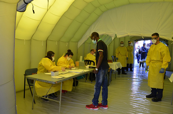 Temporeros sometiéndose a tests pcr en la carpa instalada en la plaza del Depòsit. Foto:Europa Press.