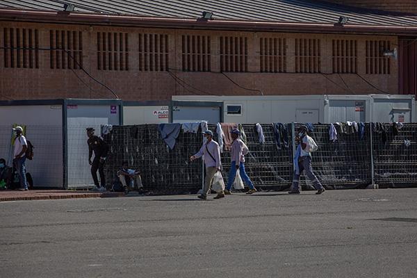 Varias personas pasean junto a un albergue para temporeros junto a la Fira de Lleida. Foto. Europa Press.