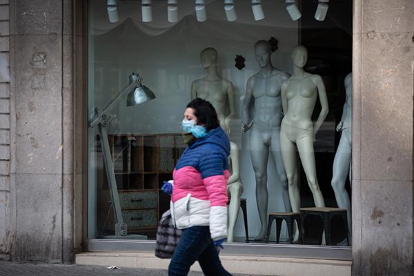 Una mujer pasea ante una tienda cerrada durante el estado de alarma. Foto: Europa Press.