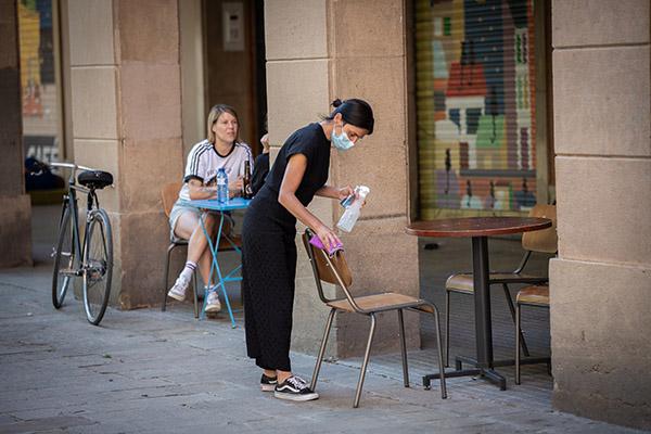 Una camarera limpia la mesa de un bar barcelonés durante el segundo día de reapertura. Foto: Europa Press.
