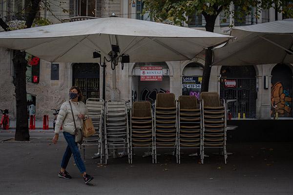 Una mujer pasea junto a una terraza cerrada en Barcelona. Foto: Europa Press.
