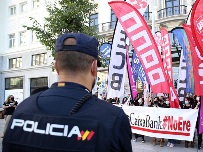 Un agente de Policía Nacional vigila a los trabajadores de CaixaBank durante el paro parcial convocado a principios de junio en Madrid. Foto: Europa Press.